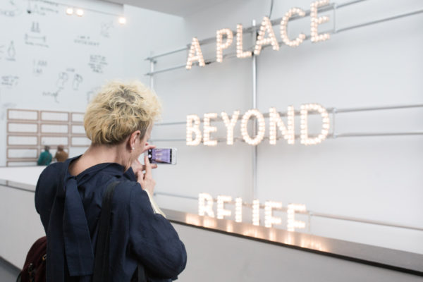 Adele Patrick stands in front of Nathan Coley's A Place Beyond Belief (2013) during visit to Van Abbe Museum, Eindhoven in 2018